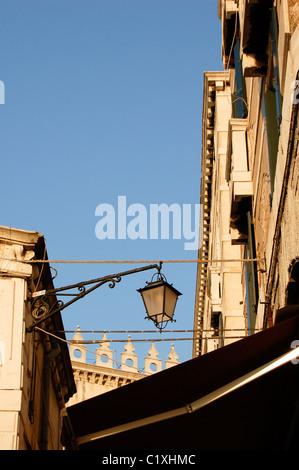 A lamp on the Rialto Bridge against a blue sky, in warm near sunset light, Venice, Italy - Stock Photo