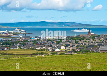 A general view over Kirkwall in Orkney towards the harbour with cruise ships at the pier and anchored in Kirkwall - Stock Photo