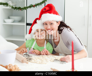 Portrait of a cute girl with her mother baking Christmas cookies - Stock Photo