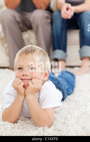 Cute little boy lying on the floor and watching television with his parents - Stock Photo
