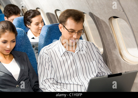 Photo of pretty woman with handsome man typing next to her in airplane - Stock Photo