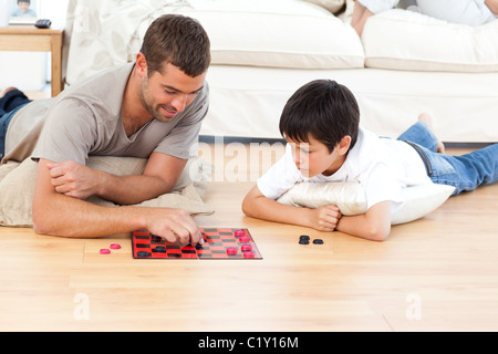 Handsome man playing checkers with his son lying on the floor - Stock Photo