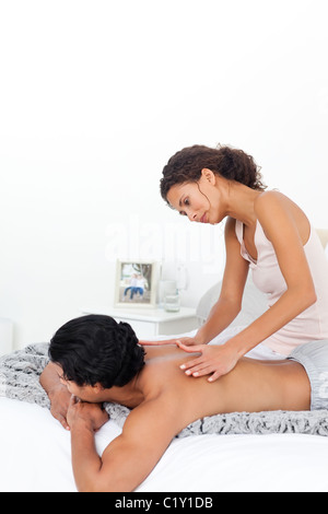 Attentive woman doing a massage to her boyfriend on their bed - Stock Photo