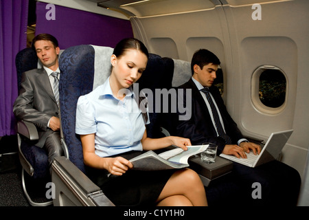 Image of pretty girl reading magazine while handsome man typing next to her - Stock Photo