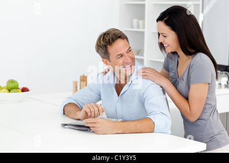 Happy couple doing a cryptic crossword together - Stock Photo