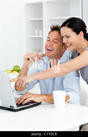Happy woman showing something on the laptop to his boyfriend - Stock Photo
