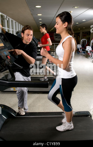 Woman, hold, holding, stand, standing, on, a, treadmill, track, at, gym. - Stock Photo