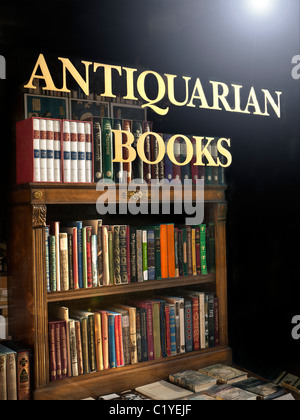 Antiquarian Bookshop window with sign and antique old books and bookcase on display with sun flaring on window glass - Stock Photo