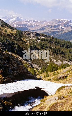 MELTING SNOW BRIDGE over Rui Gros through Clot de L'Os in mountains from Pas de les Vaques to Soldeu in early summer. - Stock Photo