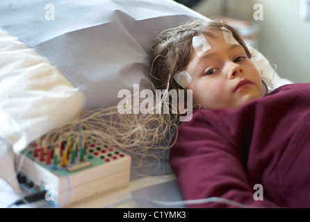 Child in a hospital out patient department undergoing an EEG or brain scan - Stock Photo