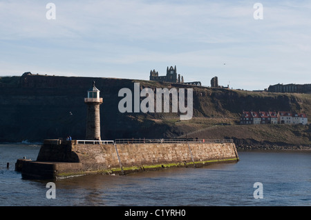 A view of the southern pier and its lighthouse that signal the harbor of Whitby, North Yorkshire, England. - Stock Photo