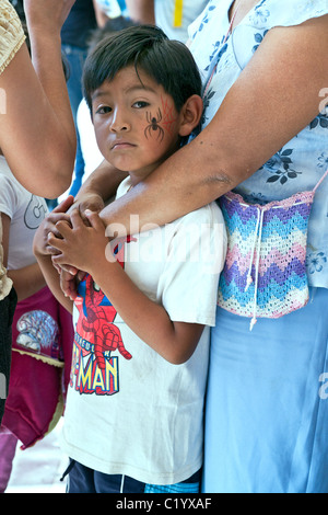 small Mexican boy in spiderman tee shirt with painted spider tattoo on his cheek safely holding onto his mother - Stock Photo