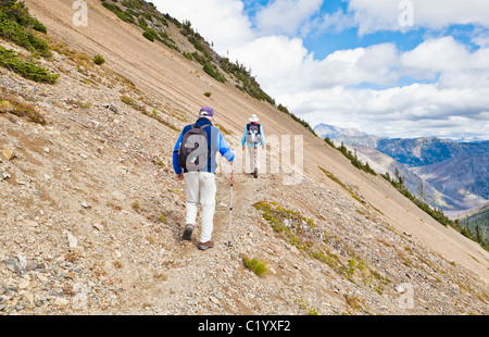 Two men walking along a mountainside on a narrow trail. Pacific Crest Trail, North Cascades of Washington, USA. - Stock Photo