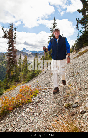 A man walking along a mountainside on a narrow trail. Pacific Crest Trail, North Cascades of Washington, USA. - Stock Photo