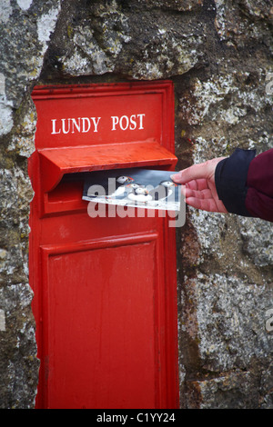 Posting a postcard with puffins on in the Lundy Post post box on Lundy Island, Devon, England UK in March - Stock Photo
