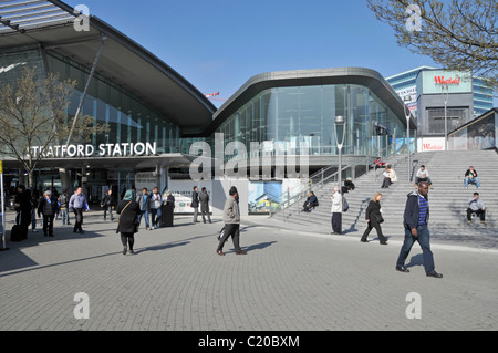 People in East London street scene & steps up to Westfield Stratford shopping centre beside extended train railway - Stock Photo