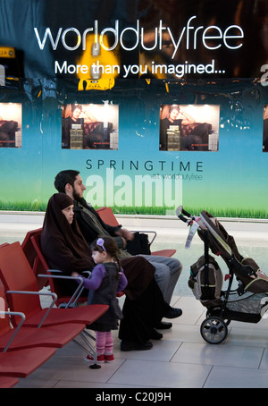 A muslim family waiting in Departures, seen against the world duty free shop, terminal 5, heathrow airport, London - Stock Photo