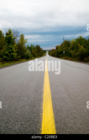 Rural paved road leading to city - Stock Photo