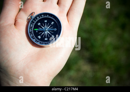 Classic compass on man's hand somewhere on trail during hiking. Green grass as a blurred background. - Stock Photo