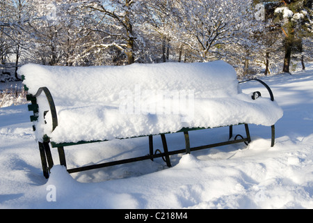 A park bench seat covered in lots of snow. - Stock Photo