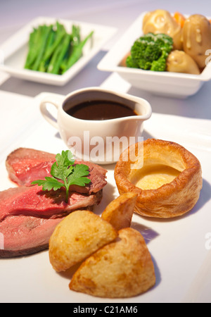 Traditional rare roast beef sunday dinner with vegtables and gravy. - Stock Photo