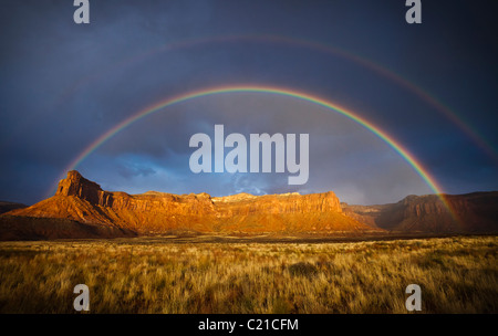 A rainbow and storm clouds over mesas and desert grasslands in southeastern Utah, USA. - Stock Photo