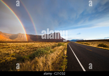 Highway 211, mesas, and a rainbow in the desert of Southeast Utah, USA. - Stock Photo