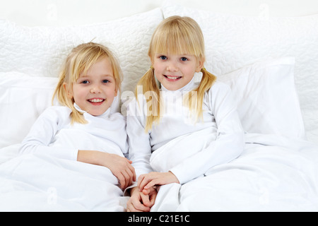 Portrait of cute twins lying in the bed - Stock Photo