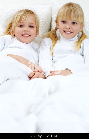 Portrait of two adorable sisters lying in the bed - Stock Photo