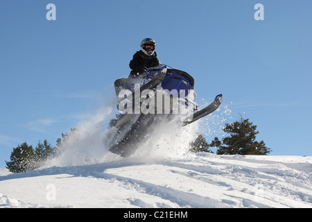 man and fast action snowmobile jumping - Stock Photo