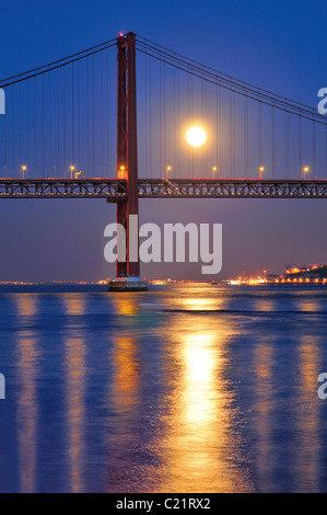 Portugal, Lisbon: Ponte 25 de Abril over river Tagus  with full moon - Stock Photo