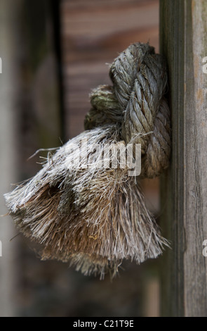 Firmly knotted rope is pressed against its post hole in a knotty problem metaphor. - Stock Photo