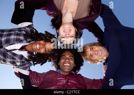 A group of friends hugging in a circle and looking at the camera - Stock Photo