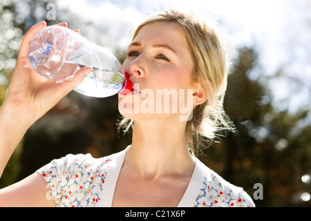 Woman drinking bottled water - Stock Photo