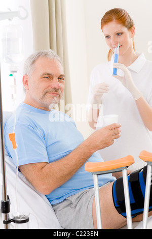 Hospital - female nurse give injection patient with broken leg - Stock Photo