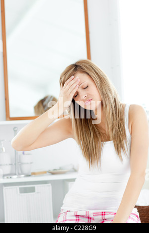 Dejected woman having a headache sitting in the bathroom - Stock Photo