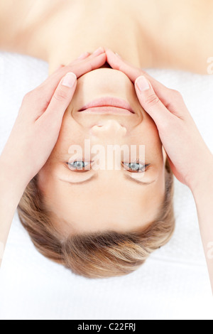 Positive woman receiving a facial massage smiling at the camera - Stock Photo