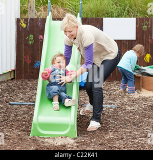 Little girl and her beautiful mother having fun with a chute - Stock Photo