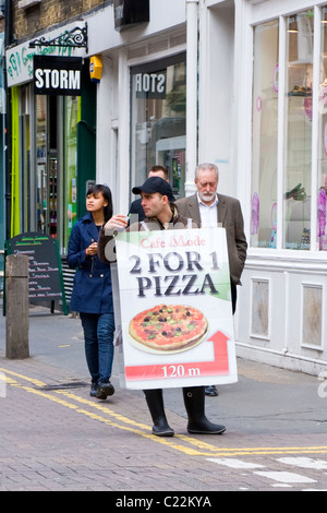 London , Covent Garden , sandwich board man , in baseball cap , Cafe Mode , 2 for 1 pizza offer - Stock Photo