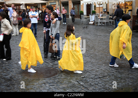 mother and two daughters wearing rainproof bright yellow ponchos - Stock Photo