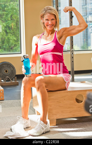 Portrait of a physically fit woman in a weightroom / healthclub setting. - Stock Photo