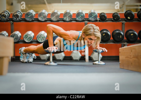 Physically fit woman doing push-ups on dumbbells in a health club. - Stock Photo