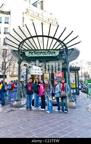 A tour group young people pose for a photo in front of an art-nouveau Metropolitain Metro sign; Paris France. Charles - Stock Photo