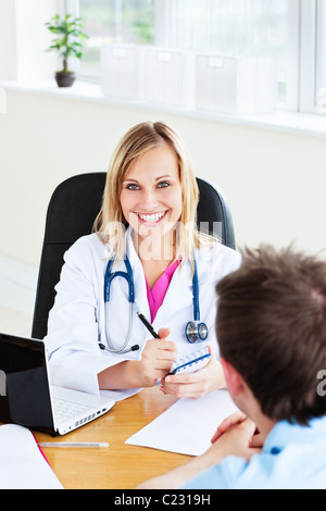 Smiling female doctor writing a prescription for her patient in the office - Stock Photo
