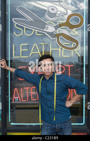 Man standing infront of laundrette shop window - Stock Photo