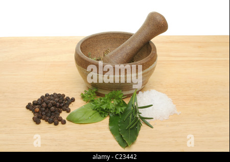 Fresh herbs,sea salt, pepper corns with a pestle and mortar on a wooden board - Stock Photo