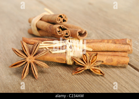 Cinnamon and star anise spices on old weathered and cracked wood with selective shallow focus - Stock Photo