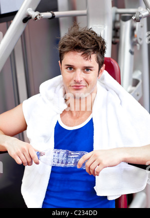 Handsome man sitting on a bench press  after exercises - Stock Photo