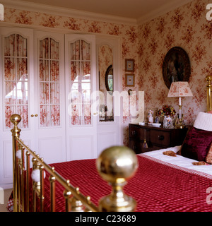 Red Quilt On Brass Framed Bed In Bedroom With Toile De Jouy Wallpaper    Stock Photo