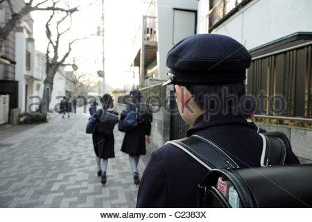 young school boys and girls in uniform walking on the street Japan Kamakura - Stock Photo